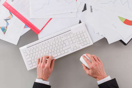 Caucasian businessman working at office. Male hands working with computer keyboard and documents on the table.