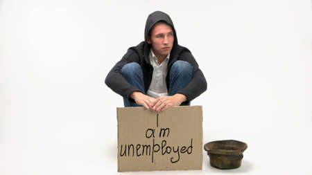 Sad young man lost his job and begs donations. Card board with I am unemployeed sentence. Isolated on white background.