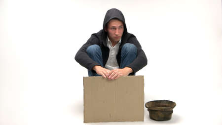 Sad jobless man with blank cardboard for copy space. Young caucasian man with hat for donations isolated on white. Financial crisis concept. Stock Photo