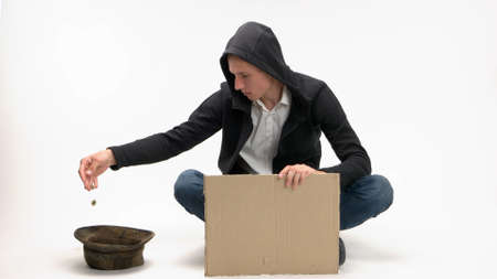 Young begging man dumps donation into his hat. Blank cardboard sign for copyspace.