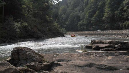 Seething waves of the mountain river. Group of tourists in a yellow boat are rafting.