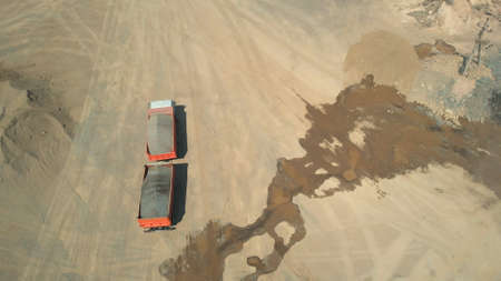 Top view of orange truck with trailer. Fossil transportation process. Wet sand on the background.