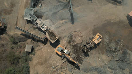 Dump truck is mooving down sand. Excavator pours soil into the truck. Stock Photo