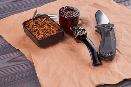 Cool smoking pipe with tobacco and knife. Composition of mens accessories.