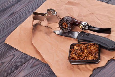 Compoistion of smoking pipe with tobacco and lighter. Grey wooden table.
