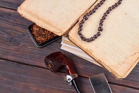 Top view vintage accessoires. Very old book with bead necklace. smoking pipe and lighter on rustic wooden table.