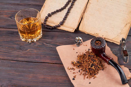 Items for leisure of adult man. Smoking pipe, , tobacco and glass of cognac on wooden table.
