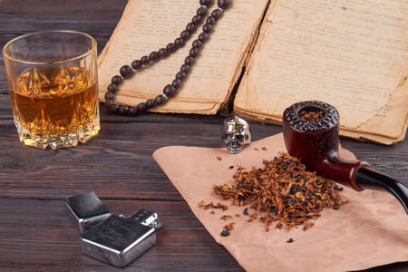 Composition of items for leisure and relax. Smoking pipe, lighter, glass of cognac and old book.