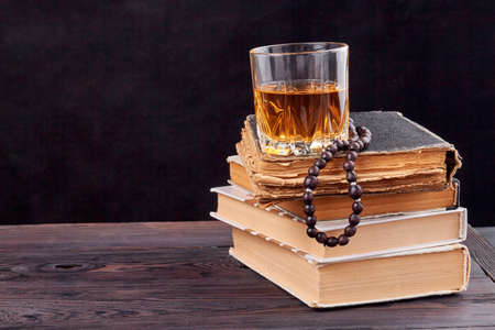 Glass of alcohol on a stack of books. Still life composition.