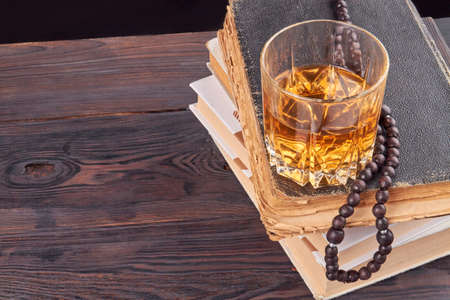 Glass cup with alcohol on a stack of books. Brown rustic wooden table. Stok Fotoğraf