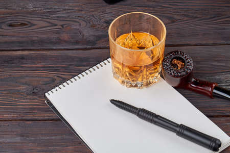 Writers stuff composition. Cup of whiskey with smoking pipe notepad and pen.