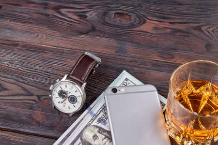 Luxury handwatch with smartphone and brandy. Top view businessman stuff on wooden table.
