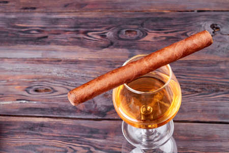 Cuba cigar and glass of brandy top view. Old rustic wooden background.