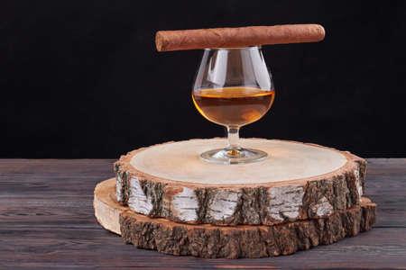 Glass of brandy with cigar. Round wooden board with bark. Dark black background.