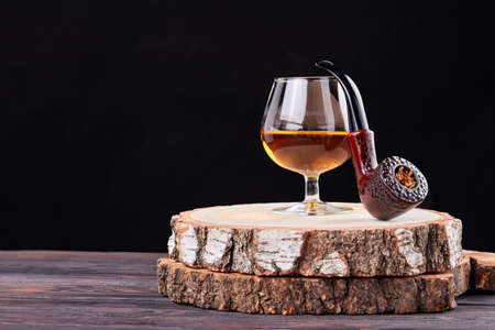 Still life glass of brandy and smoking pipe. Round wooden board with bark. isolated on black background.