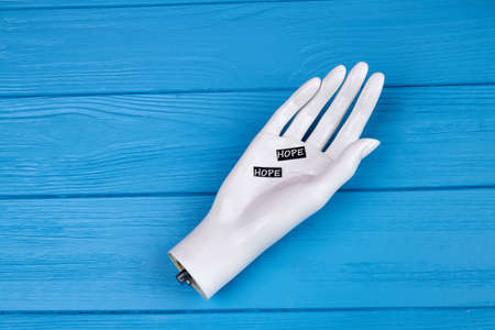 White mannequin hand with hope word. Blue wooden table.