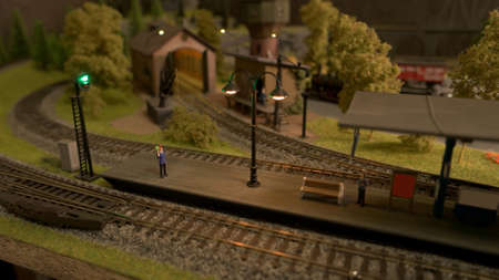 Miniature railway station and people. Retro toy railroad.
