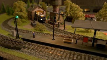 Model of retro railway station. Moniature railroad and people.