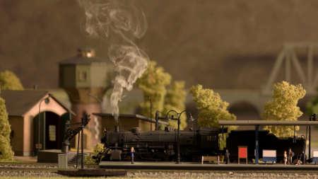 Retro railway station with lokomotive and people. Miniature model of steam train lokomotive.