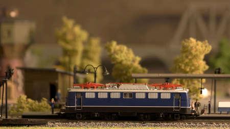 Miniature retro train model on a station Signalman and passangers. Toy plastic railway model.