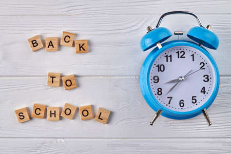 Blue alarm clock on white wood. Back to school concept.