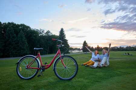 Happy mature couple sits on the lawn. Red bicycle on the grass.