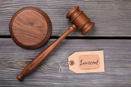 Wooden gavel and innocent verdict. Top view flat lay. Mallet on rustic wooden table.
