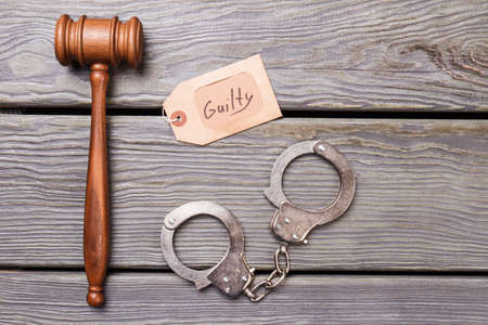 Gavel and handcuffs on wooden background. Top view flat lay. Guilty concept.