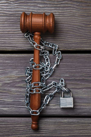 Law and legislation obstruction concept. Judge hammer or gavel surrounded by chains and locks vertical shot.