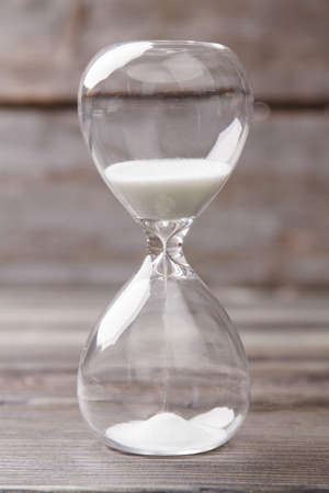 Close-up hourglass with white sand. Vertical shot old wood background.