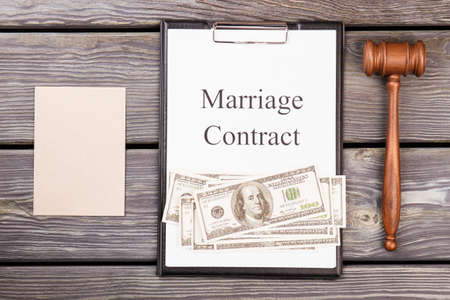 Mock marriage contract concept. Wooden gavel with money and blank paper for copy space.