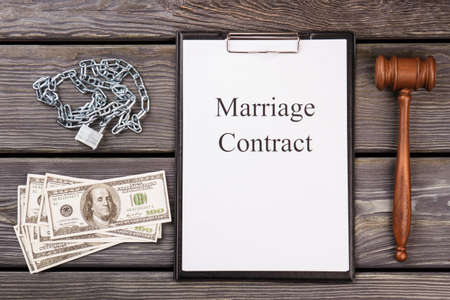 Marriage contract as a prison concept. Judge gavel with dollars and chain with padlok on wooden desk.