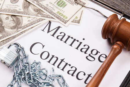 Close-up marriage contract with money and gavel. Metal chains and marriage corruption concept.