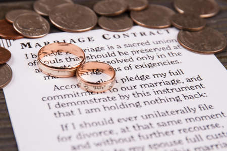 Marriage contract and wedding rings. Pile of coins.