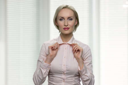 Businesswoman is dressing up and adjusting her collar. Mature middle-aged beautiful woman is getting ready for important meeting. White blurred background.
