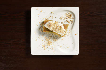 Pistachio Turkish baklava with ice cream on a square plate, top view. Photos for restaurant and cafe menus