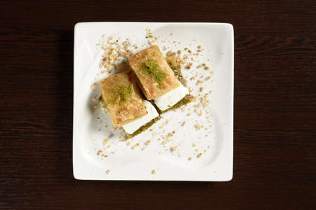 Turkish puff baklava with ice cream on square plates, top view. Turkish sweetness. Photos for restaurant and cafe menus