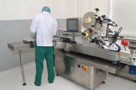 Pharmaceutical industry worker install the ampules on the labeling machine