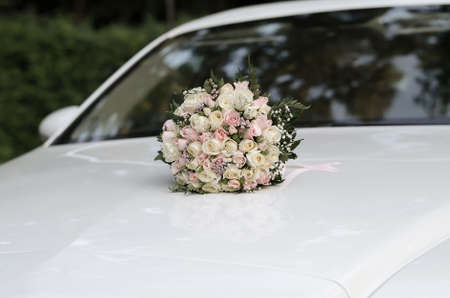 Wedding bouquet of white and pink roses on the hood of a white car