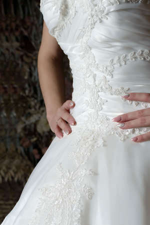 Close-up bride's dress with a beautifully embroidered pattern and hands on the waist with a beautiful manicure