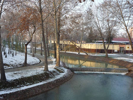 Winter landscape, river in the middle of the city park, alley and trees covered with snow