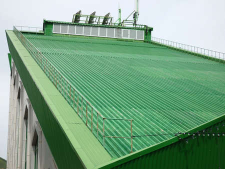 Sloping green roof of the building with a mobile communication antenna