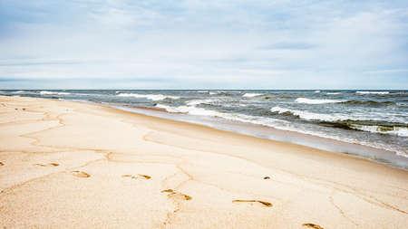 Sea waves and footprints on the sand on the beach and overcast sky, seascape