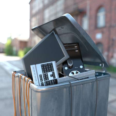 computers in a trash bin on a street