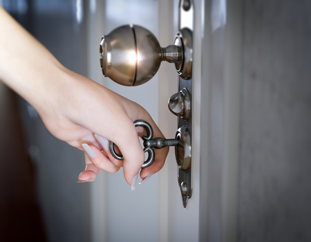 door key: woman hand opening the door conceptual composition Stock Photo