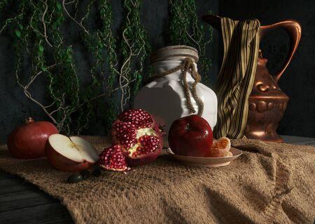 jewish home: jar, rop, apples,pomegranate,plant and orange on canvas drapery conceptual still-life