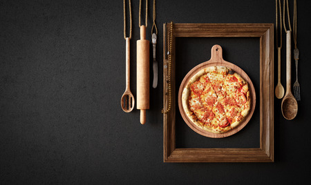 frame wall: Hot pizza slice with kitchen tools and frame concept close up photo