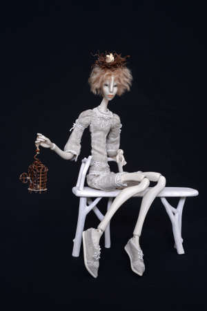 hinge joint: Porcelain doll with nest on black background Stock Photo