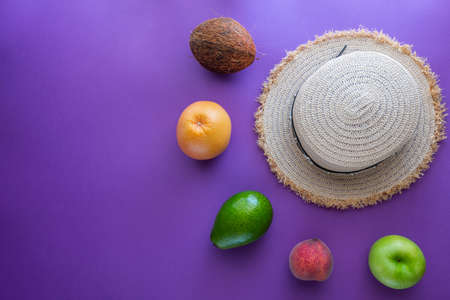 Tropical summer vacation concept with hat, coconut, avocado, peach and orange 写真素材