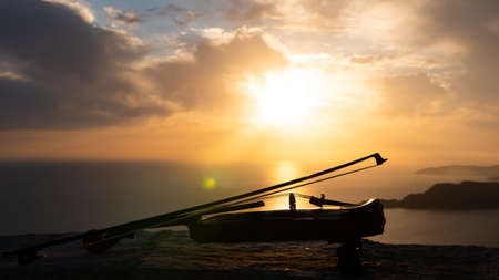 Violin with bow by the sea at sunset 写真素材